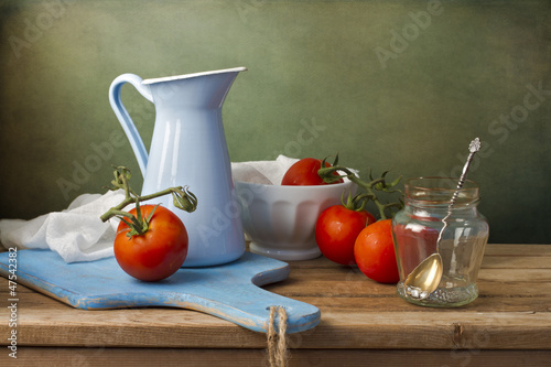 Fotografía  Still life with fresh tomatoes and tableware on wooden table