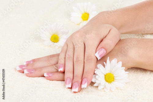 Poster Pedicure Woman hands with french manicure and flowers on towel