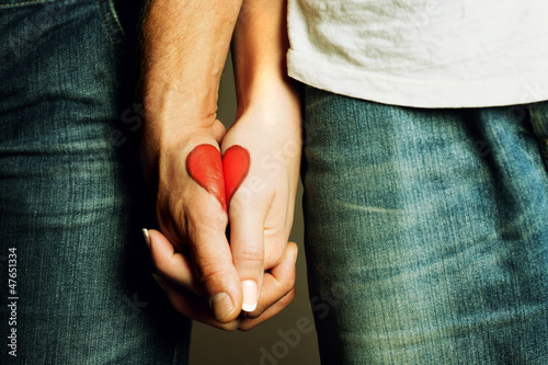 Fotografie, Obraz  In love forever, red heart drawing on hands of a couple