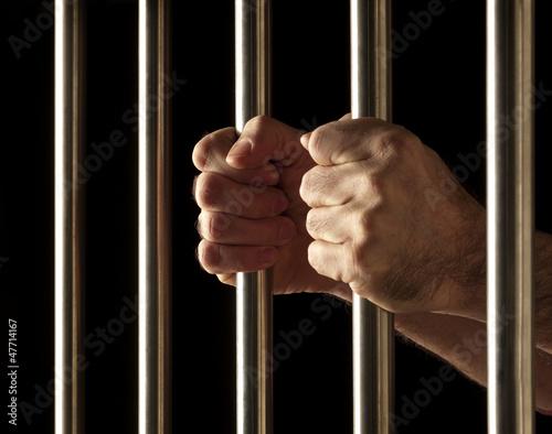Fotografia, Obraz  hands of a prisoner behind bars