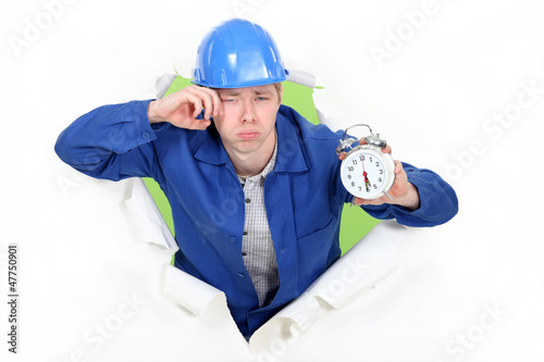 Photo Bleary eyed construction worker with an alarm clock