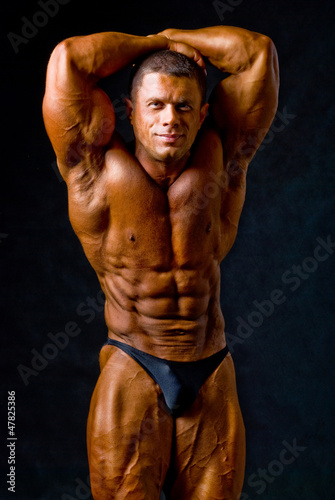 Fotografie, Obraz  Portrait of a sexy young macho man showing his strong biceps