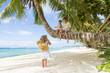 three children - boy and girls - sitting on palm tree on tropica