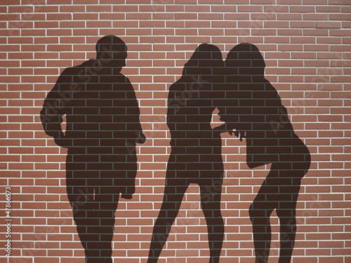 Fotografia  ombres 1 homme 2 femmes sur mur de briques