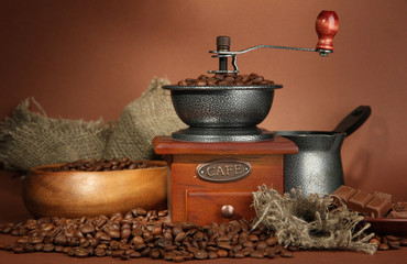 Obraz na PlexiCoffee grinder, turk and coffee beans on brown background