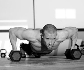 Fototapeta Gym man push-up strength pushup with dumbbell