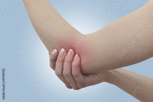Fotografía  Acute pain in a woman elbow. Female holding hand to spot of elbo