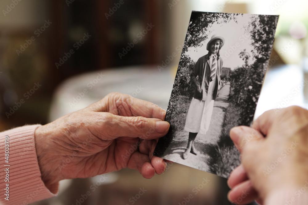 Fototapety, obrazy: Seniorin mit altem Foto aus ihrer jugend