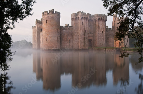 Poster de jardin Chateau Stunning moat and castle in Autumn Fall sunrise with mist over m