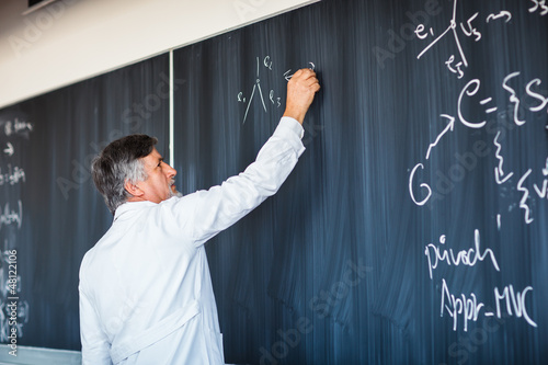 Obraz na plátně Senior chemistry professor writing on the board