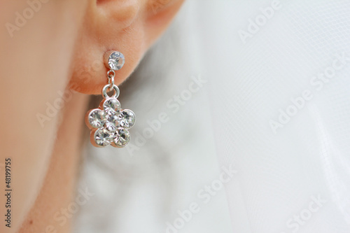 Canvas Print Earring with diamond. Woman with earring close up