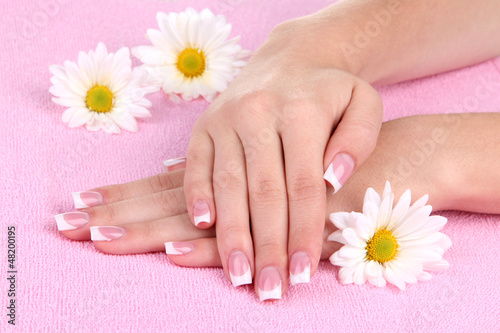 Poster Pedicure Woman hands with french manicure and flowers on pink towel