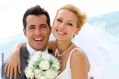 Cheerful married couple standing on the beach Fototapeta