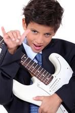 A Little Boy Playing Guitar An...