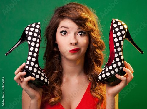 Fotografía  Funny young woman holding high heels shoes