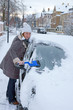 Woman remove snow from windshield