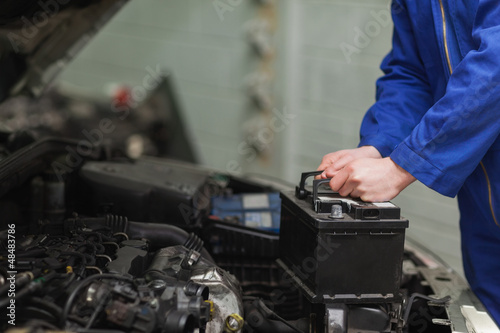 Obraz Mechanic changing car battery - fototapety do salonu