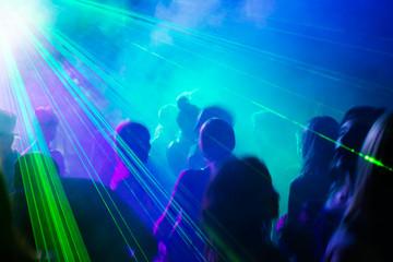 Party people dancing under laser light.