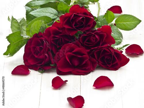 czerwona-roza-z-platkami-roz-lezacego-na-drewnianej-tacy