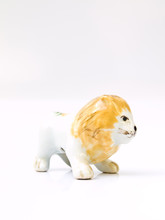 A Ceramic Lion Doll Isolated On White Background In Profile View