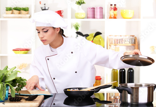 Deurstickers Ontspanning Young woman chef cooking in kitchen