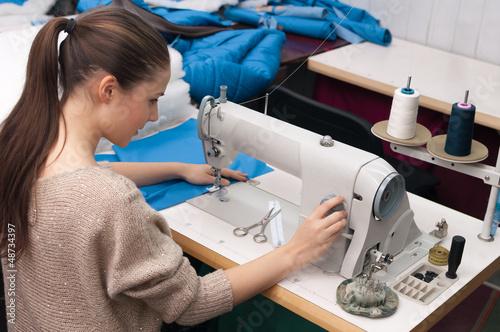 Fototapeta she sews on the sewing machine