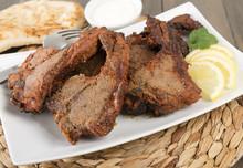 Grilled Tikka Lamb Chops With Naan, Lemon Wedges And Raita