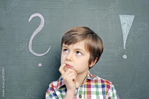 Fotografering  Kind mit Fragezeichen an Schultafel