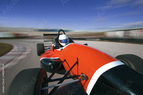 red racing car driving at high speed in circuit.Camera on board