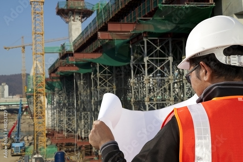 Photo  builder inspector checking plan a construction site