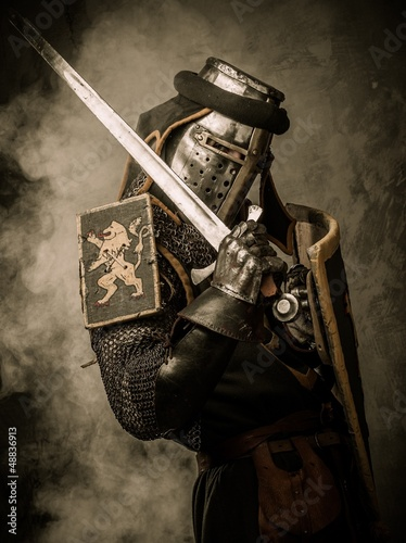 Printed kitchen splashbacks Knights Medieval knight with sword and shield against stone wall