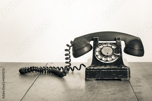 Fotografía  Vintage telephone on old table sepia photo