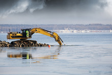 Bulldozer And Driver Dredging In The Sea