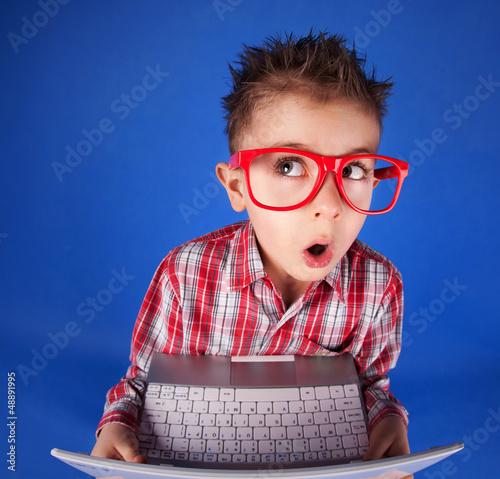 Fotografía  El niño pequeño con un ordenador portátil, el concepto de adicción a la computad