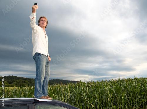 Fotomural  Mann steht auf Autodach ohne Netzabdeckung