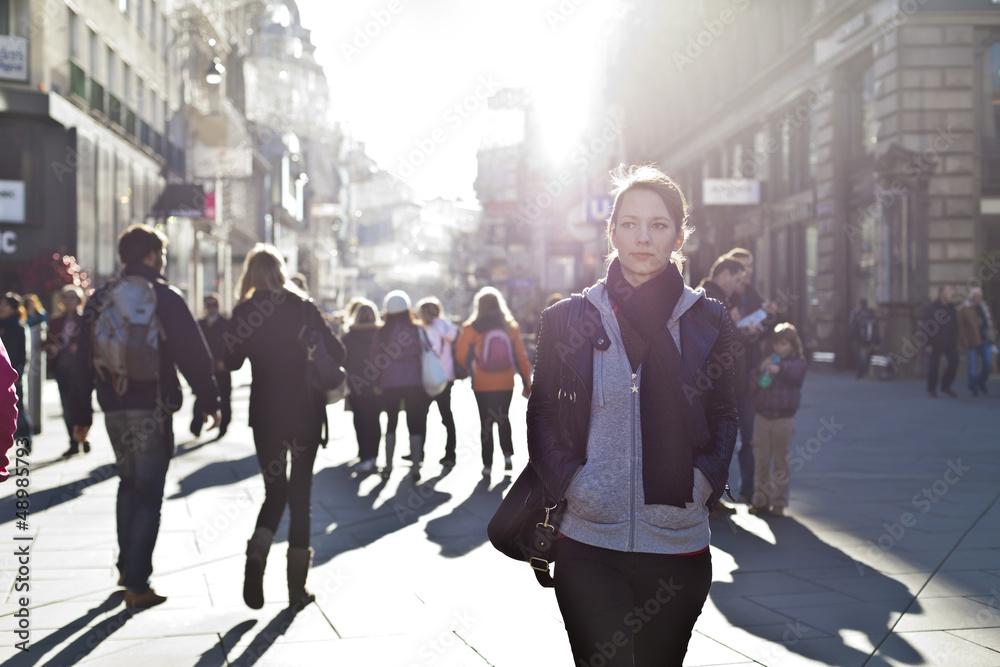 Fototapeta Urban girl striding through city area