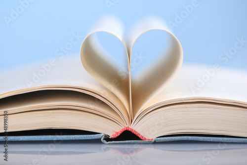 In de dag Hert Pages of a book curved into a heart shape on blue background