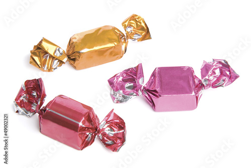 Fotomural Three wrapped candies or sweets on a white background.