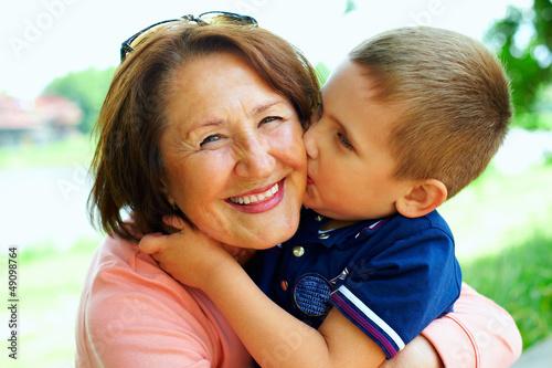 Fotografiet happy grandma with grandson embracing outdoor