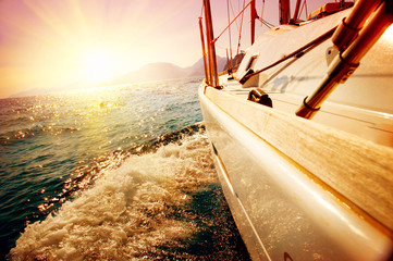 Obraz na Szkle Optyczne powiększenie Yacht Sailing against sunset. Sailboat. Yachting. Sailing