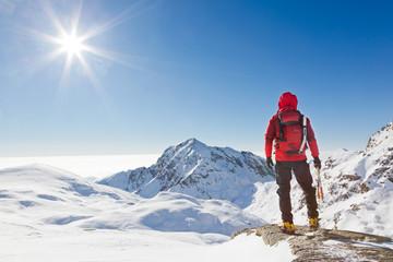 Planinar koji gleda snježni planinski krajolik