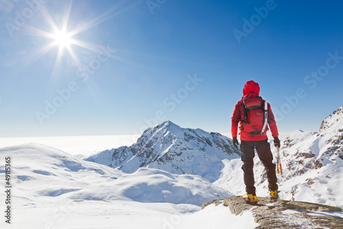 Poster Wintersporten Mountaineer looking at a snowy mountain landscape