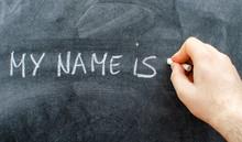 Teacher Writing His Name On Blackboard