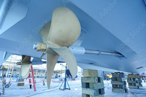 Juliste  boat propeller up on blocks in boat yard