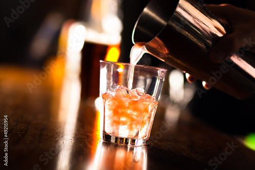 Foto op Aluminium Alcohol Hands of a bartender pouring a drink into a glass