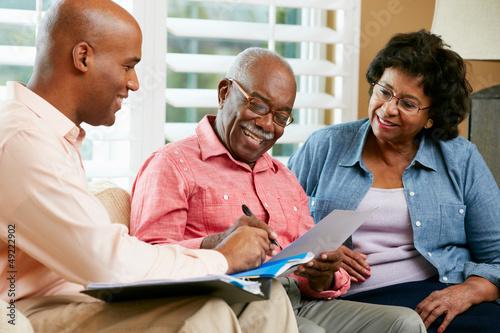 Fotografía  Financial Advisor Talking To Senior Couple At Home