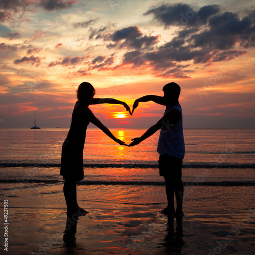 Papiers peints Corail Young couple holding hands heart-shaped on the sea beach.