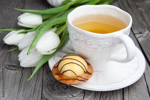 cukierki-tort-z-filizanka-herbata-i-kwiaty-na-drewnianym-t