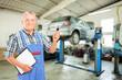 Mechanic holding a car key atauto repair shop during an automobi