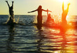 canvas print picture - Silhouettes of people jumping in ocean